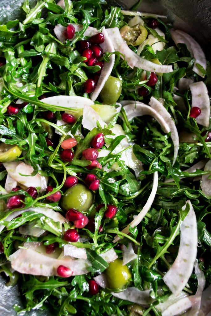 arugula salad being tossed