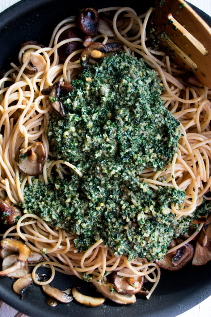 kale pesto being tossed with spaghetti