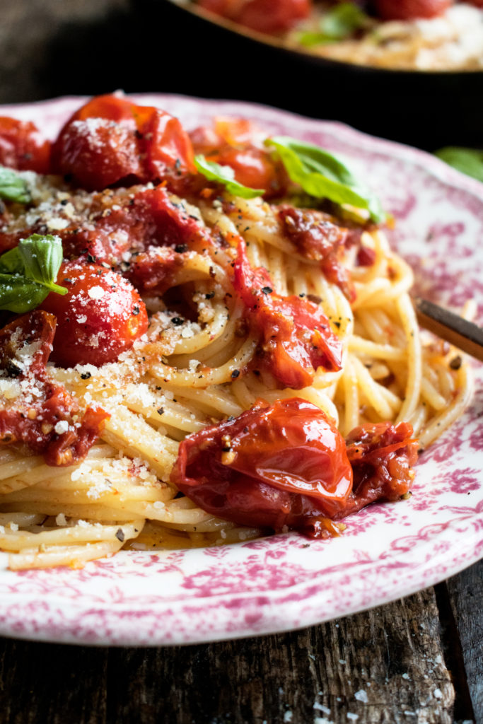Tomato Confit Spaghetti. A really simple summer pasta recipe that highlights sweet tomatoes in a rich & savory way. Topped with lots of parmesan and basil!